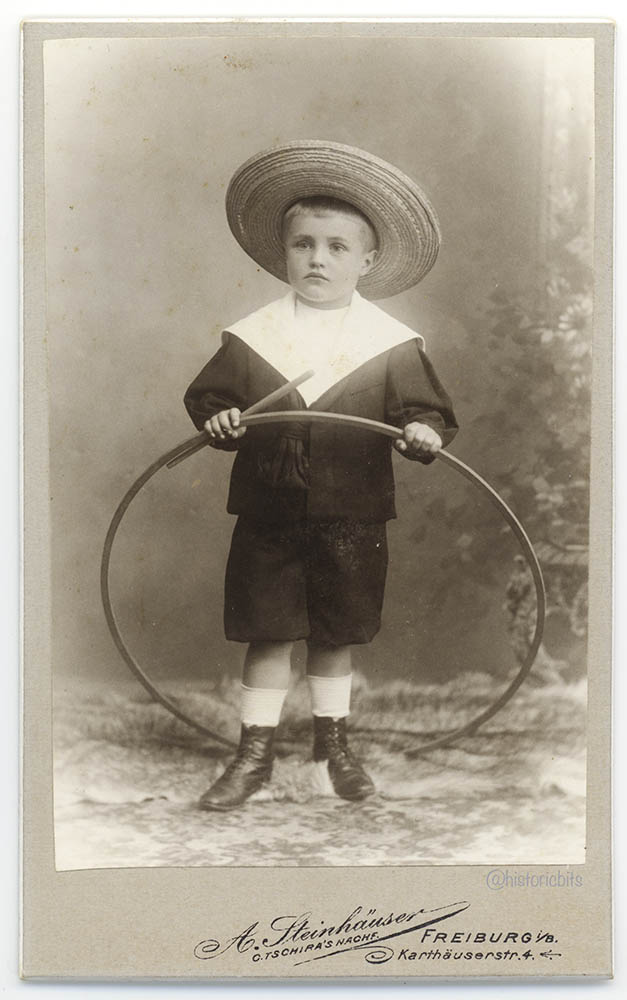 Child with trundling hoop, Germany,c.1890